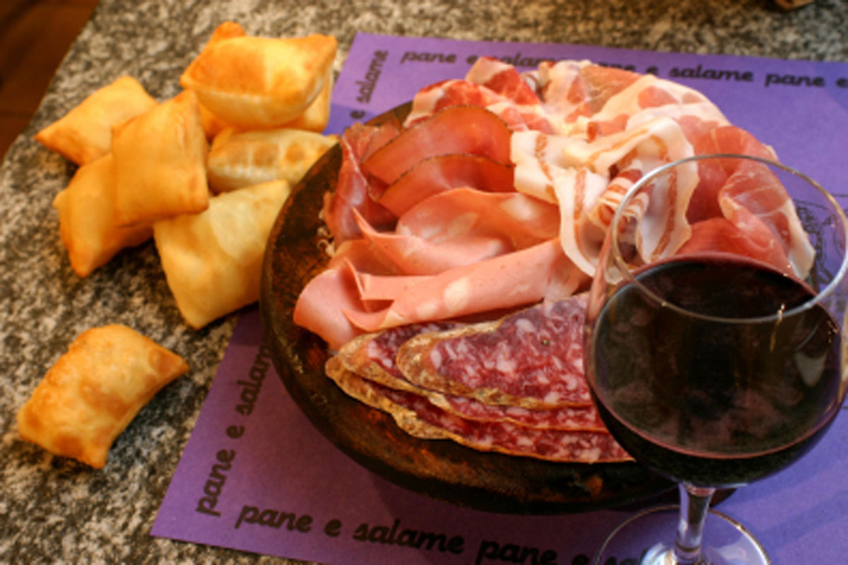 Bicchiere di vino con gnocco e salume